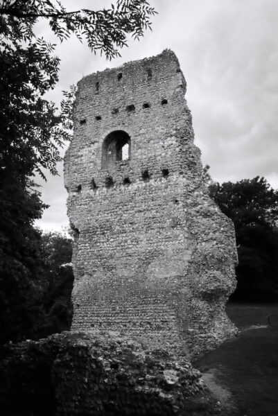 A very small section of a tall castle wall stands in a field
