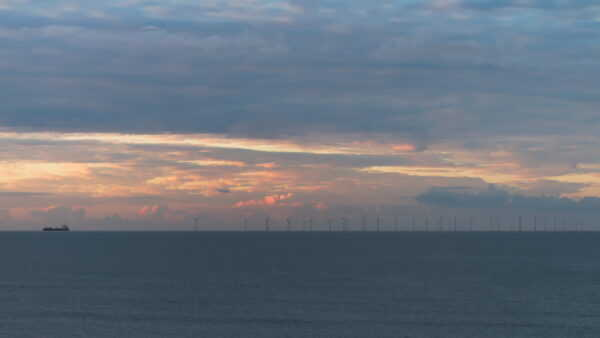 A container ship on the horizon has just passed the windmills of Rampion windfarm against a dramatic dawn sky