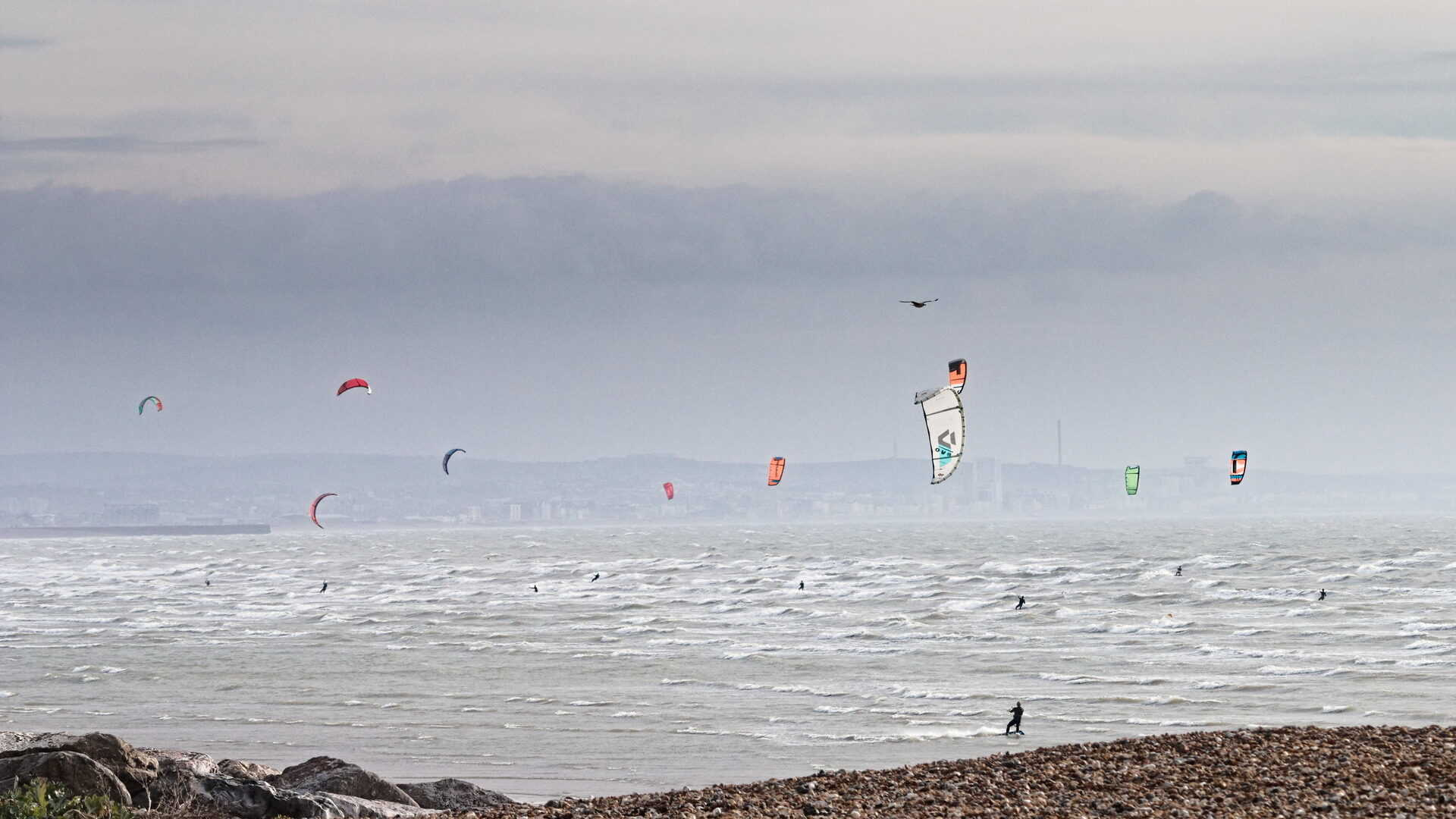 the choppy shoreline of Shoreham bay is peppered with brightly coloured kite surfer kites.