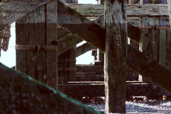A close up of ancient support beams of a wooden bridge over the river