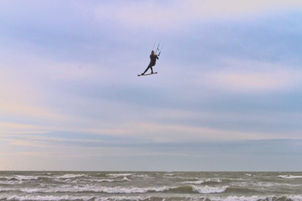 A kite surfer hangs high in the air above the surf