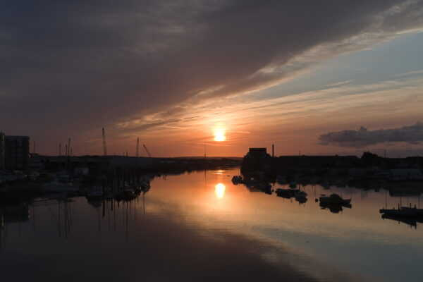 A dramatic sunrise is reflected in the river Adur at Shoreham